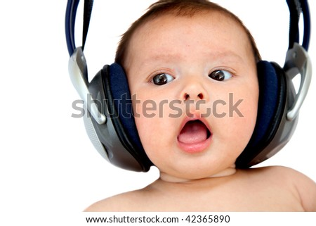 Cute baby with earphones listening music isolated on white