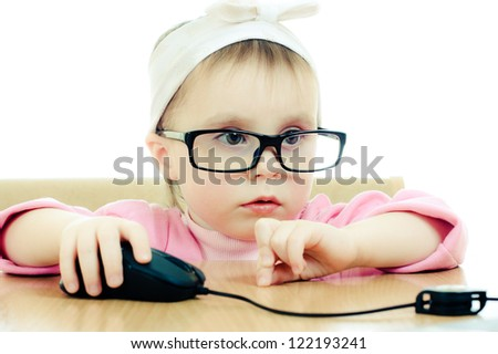 Cute baby with glasses looking into the laptop on a white background.
