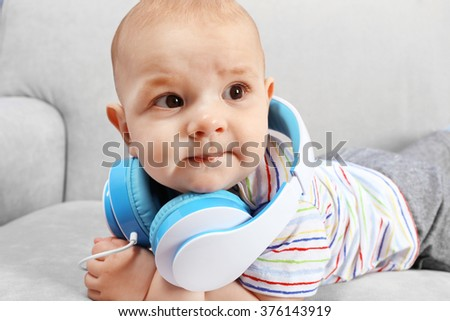 Cute baby with headphones on comfortable sofa in the room, close up