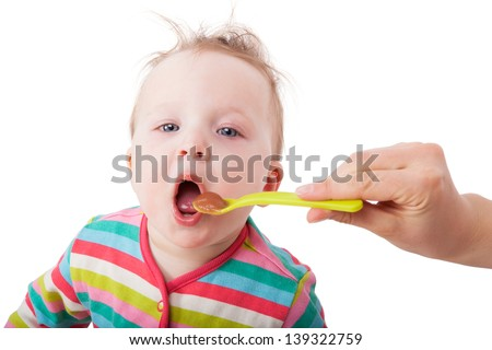Cute baby with open mouth eating. Mother hand holding spoon. Isolated on white background. - stock photo