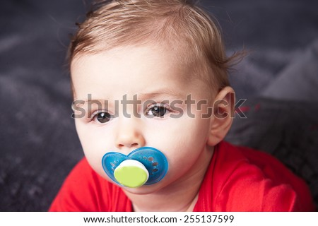 Cute baby with pacifier - stock photo