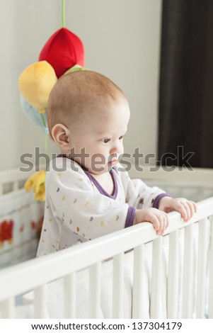 Cute baby with serious face standing in a cot in child�s room - stock photo