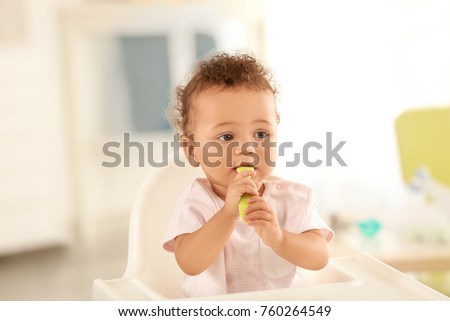Cute baby with spoon sitting in room