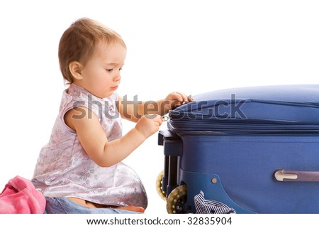 Cute baby zipping the suitcase for summer vacations, isolated - stock photo