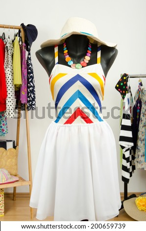Cute beach outfit with suimsuit and hat on a mannequin. Dressing closet with colorful summer clothes and accessories on hangers.  - stock photo