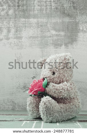 cute bear doll holding rose bouquet - stock photo