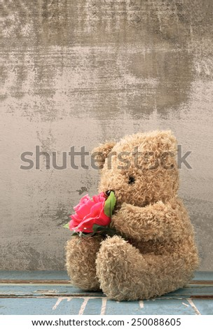 cute bear doll holding rose bouquet in vintage style - stock photo