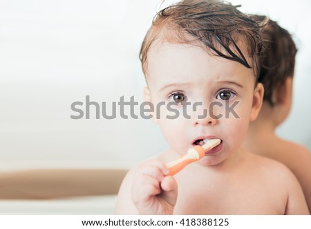 Cute beautiful boy at the bathroom washing his teeth - stock photo