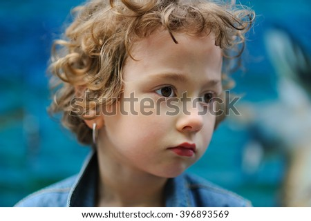 Cute, beautiful curly little girl close-up portrait outdoors. Serious toddler child, kid on a sunny day looking away on the nature at summer or spring on the blue background. Fashion and beauty. - stock photo