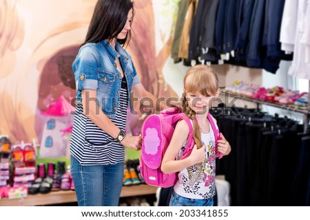 Cute beautiful little girl with her mother to buy clothes in shop - stock photo