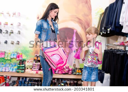 Cute beautiful little girl with her mother to schoolbag  shop
