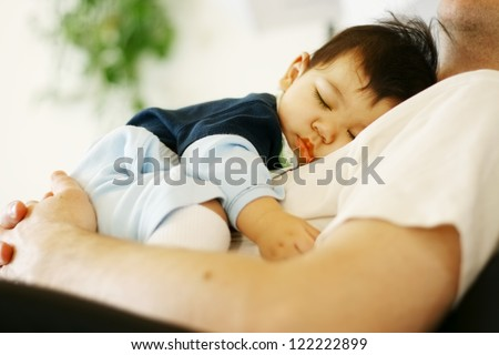 Cute biracial baby boy asleep on father's chest - stock photo