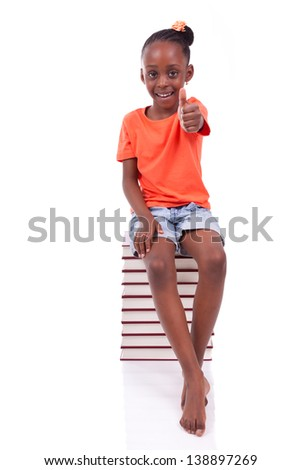 Cute black african american little girl seated in a stack of books making thumbs up, isolated on white background - African people - Children