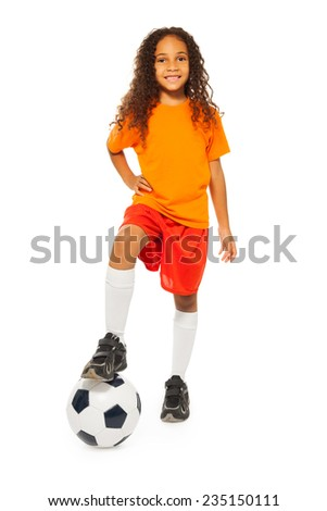 Cute black girl stand on soccer ball in studio - stock photo