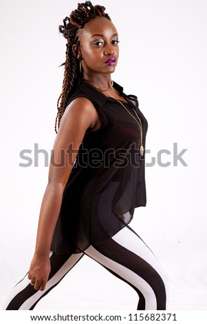 Cute black woman in black and white striped pants,  looking into the camera with a serious expression - stock photo
