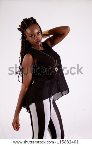 Cute black woman in black and white striped pants, with her hand behind her head and looking into the camera with a serious expression - stock photo