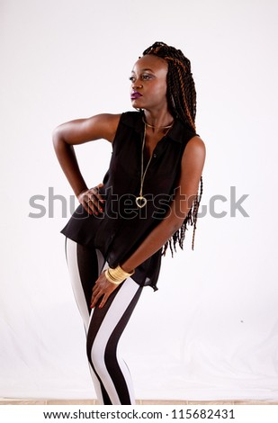 Cute black woman in black and white stripped ants, leaning back and looking left with a serious expression - stock photo