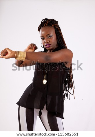 Cute black woman in black and white stripped ants, with her hand on her thigh, and looking into the camera with a serious expression - stock photo