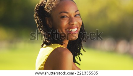 Cute black woman smiling in a park - stock photo
