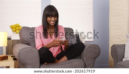 Cute black woman using smartphone on couch - stock photo