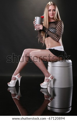 Cute blond and silver cold drink cup sits on silver bucket - stock photo