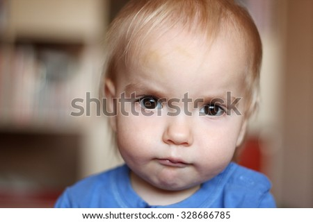 Cute blond baby boy with serious fun grimace and tightened mouth, indoor portrait - stock photo