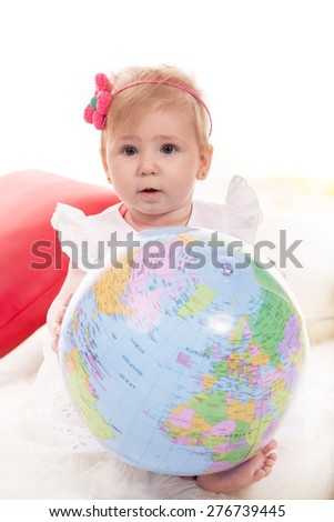 Cute blond baby girl holding World globe and sitting on  blanket - stock photo