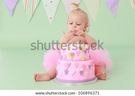 Cute blond baby girl in a pink tutu and ponytail sitting on a green background playing with icing in her hands from her double tier green pink and purple fondant iced heart birthday party cake