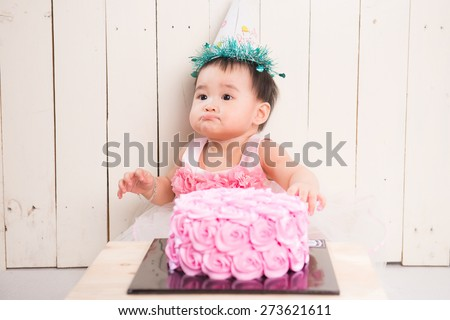 Cute blond baby girl in pink tutu and ponytail sitting on green background by birthday party double tier pink and purple fondant iced cake with hands in cake happy and excited to celebrate and eat it - stock photo