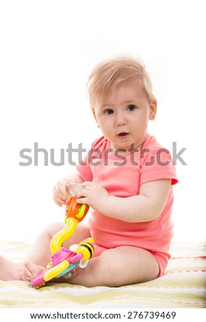 Cute blond baby girl playing with toys and sitting on blanket - stock photo