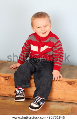 Cute blond baby wearing a red jersey against blue - stock photo