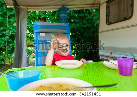 Cute blond boy eating lunch in the camp. - stock photo