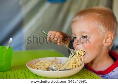 Cute blond boy eating spaghetti (Shallow DOF). - stock photo