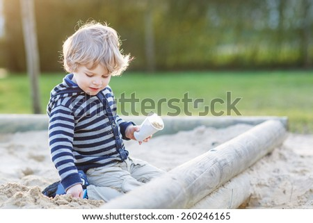 Cute blond boy having fun with sand on outdoor playground. Active leisure with kids in spring or summer. - stock photo