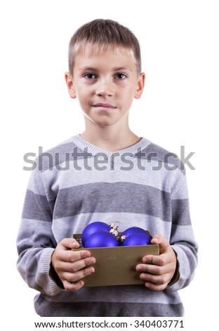 Cute blond boy holding a box with Christmas toys. Isolated on white background.