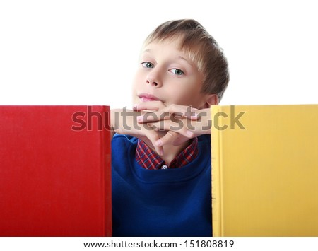 Cute blond boy in a blue sweater sitting behind two colorful hardcover books bored and thinking (isolated on white background)  - stock photo