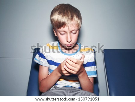Cute blond boy in a colorful t-shirt types a message on a mobile phone sitting in an airport terminal  - stock photo