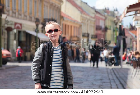 Cute blond boy in sunglasses in old european city - stock photo
