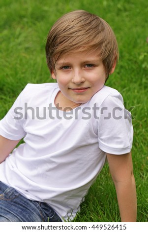 cute blond boy is lying on green grass in the park  - stock photo