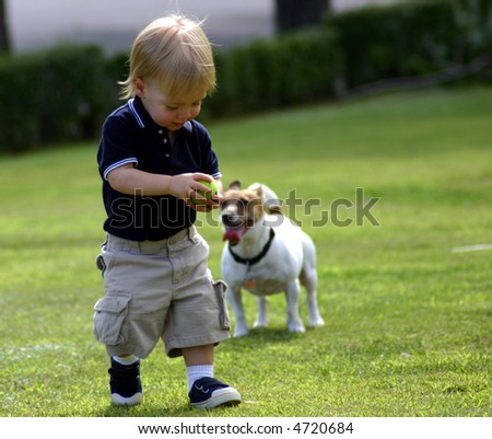 Cute blond Boy one year old  playing with his dog, ball - stock photo
