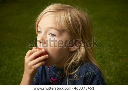Cute blond child girl eating tomato outside in the garden