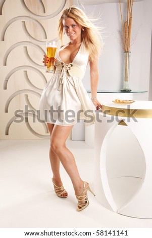 Cute blond enjoys a beer at the lounge - stock photo