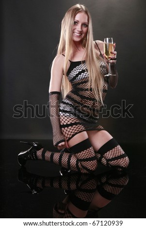 Cute blond enjoys a champagne flute on a reflective floor - stock photo