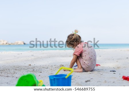 cute blond girl in elementary school age playing with bright  sand toys on paradise destination beach with blue water during summer vacation