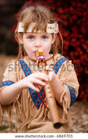 Cute blond girl in native American attire playing a wooden flute.