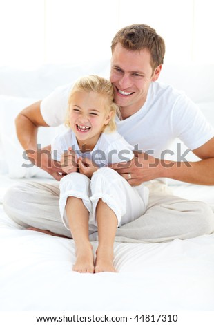 Cute blond girl laughing with his father - stock photo