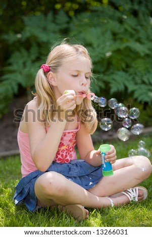 Cute blond girl outdoors blowing soap bubbles - stock photo