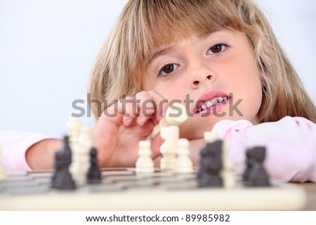 Cute blond girl playing chess