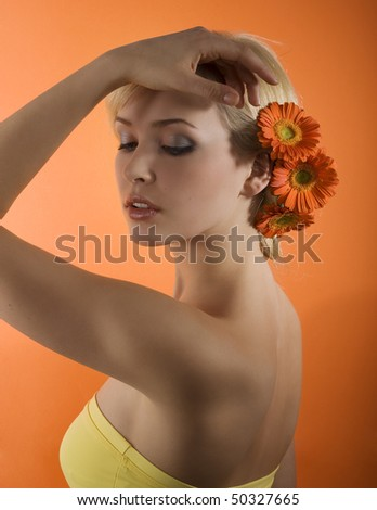 cute blond girl posing against orange background with some gerbera flowers on her head - stock photo