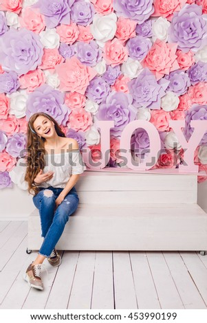 Cute blond girl sitting on a bench in a studio smiling widely. She has long curly hair and wears blue jeans and white t-shirt off the shoulder.She has pink background covered in flowers with word JOY. - stock photo